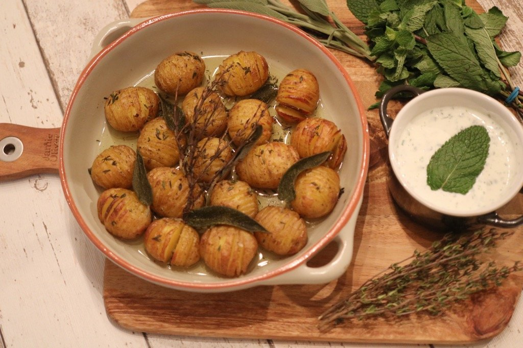 Roasted Hassleback Potatoes garnished with Sage and Thyme served with a Mint and Lime Dip